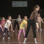 Grupa dziewczynek ćwiczy figury taneczne. Na pierwszym planie instruktorka w brązowej bluzce i czarnych spodniach