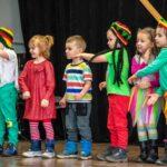 Sześcioro kolorowo ubranych dzieci stoi w rzedzie na scenie