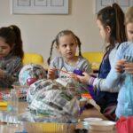 Grupa dzieci na zajęciach plastycznych. na stołach leży dużo przyborów