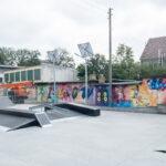 Plac z urządzeniami do jazdy na deskorolce. W tle kolorowy mural i budynki