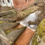 Betonowa konstrukcja na rzece. Z tułu mur z czerownej cegły
